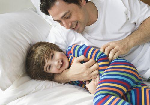 Dad tickling little boy in bed