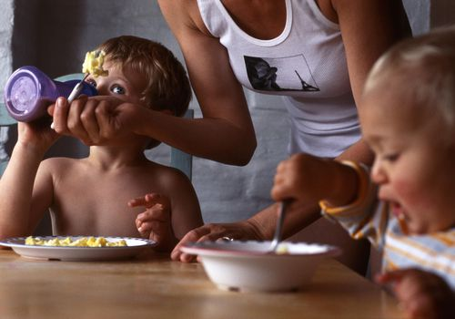 Mother helping children with breakfast