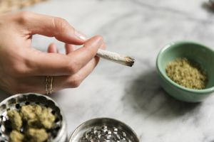 Woman's hand holding marijuana joint next to herb grinder