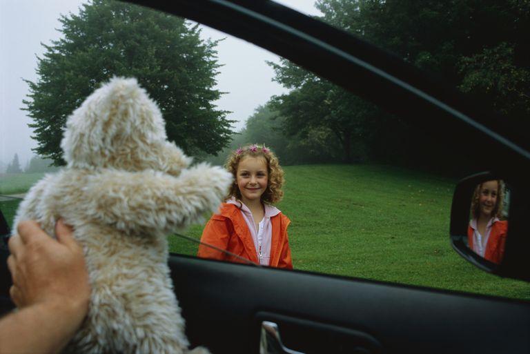 Stranger giving a girl a stuffed animal