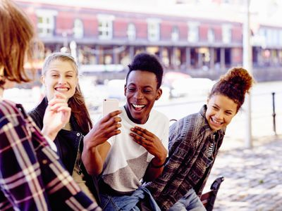 teenagers laughing and taking selfies outdoors