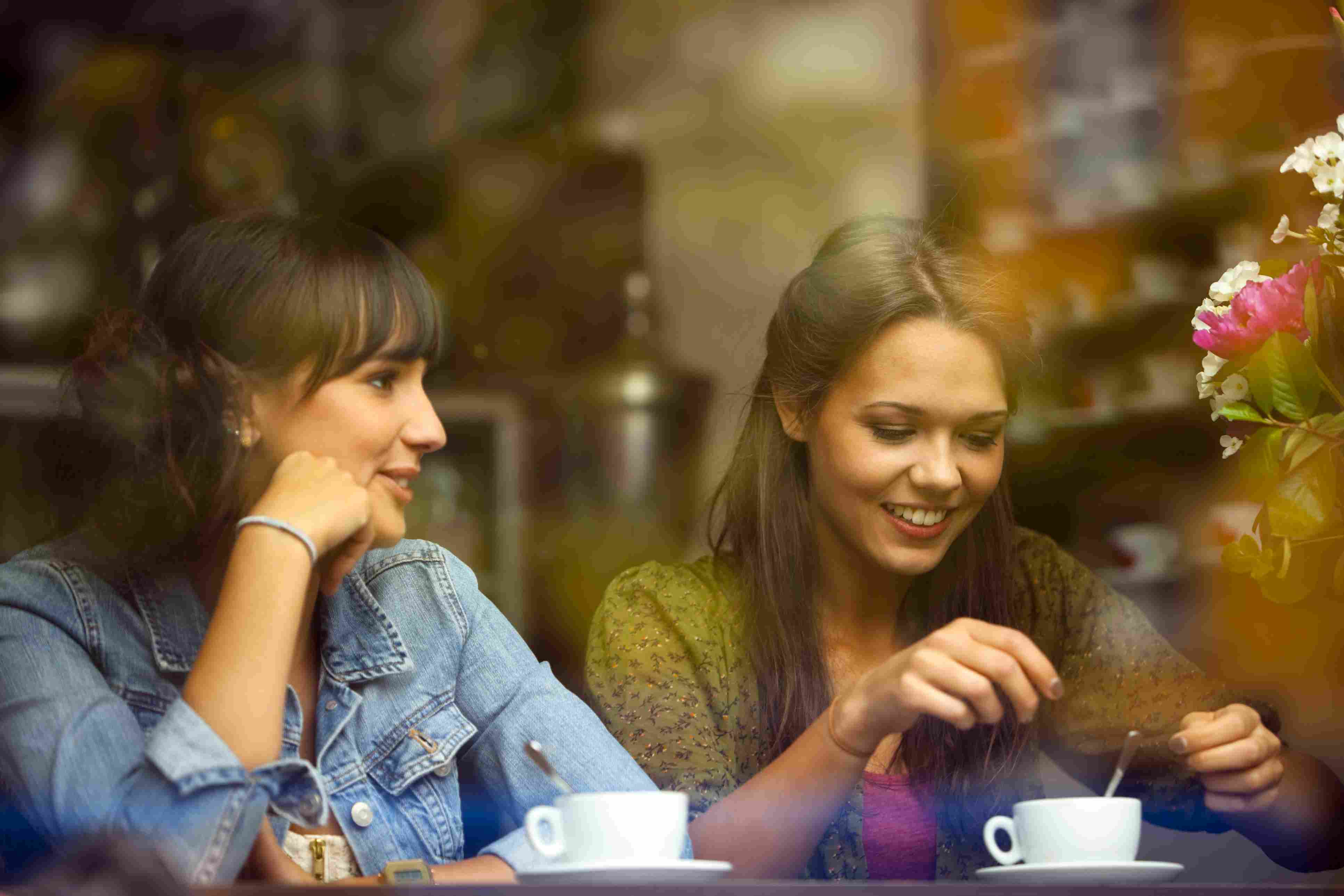 two female friends chatting in a cafe