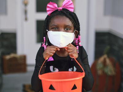 Young trick or treating girl holds bucket wearing a mask