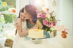 Affectionate daughter giving flower bouquet to mother on Mother's Day