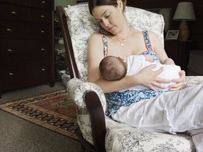 Mother nursing baby at home