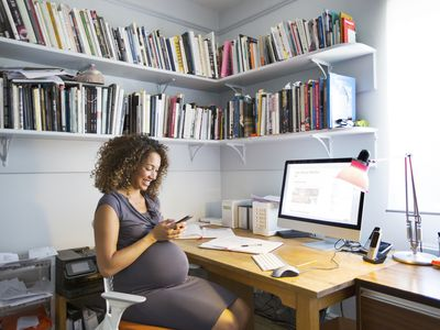 A mixed race pregnant woman works from home sitting at her desk using computer.