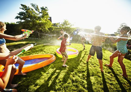 Kids having fun with squirt guns in a backyard