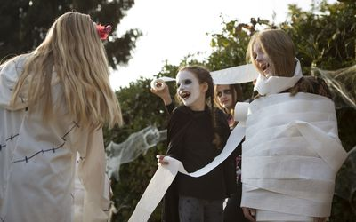 Group of older children playing 'wrap the mummy' Halloween game with toilet rolls