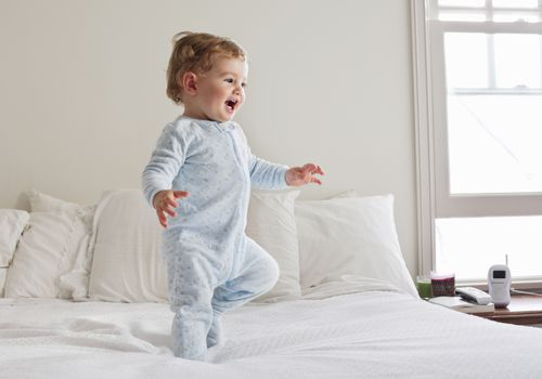 Smiling baby walking on bed