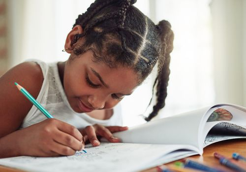 School-aged girl coloring in a coloring book