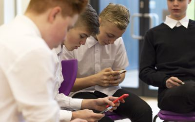 Boys in a classroom using smartphones