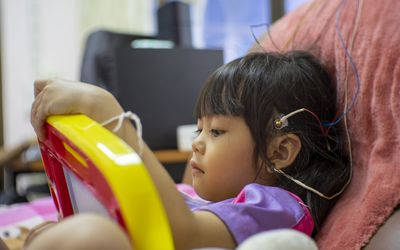 Cute Girl With Electrodes On Head Relaxing On Chair