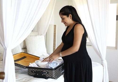 Pregnant woman packing suitcase.