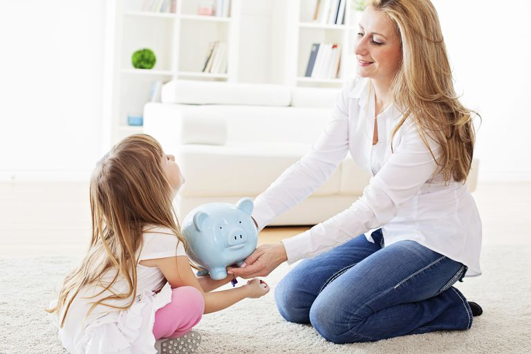 Mother and daughter holding piggy bank