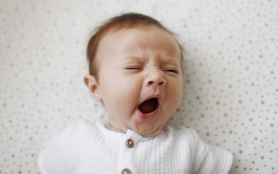 A 4 month old baby girl yawning - stock photo