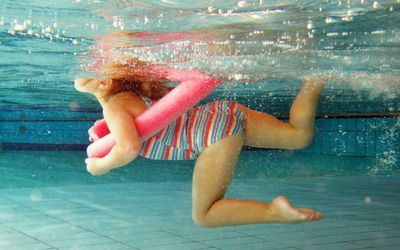kid swimming with pool noodle