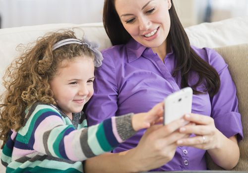 Mother and daughter using mobile phone together