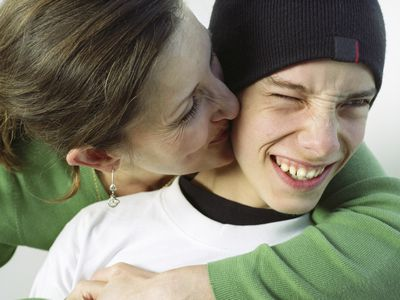 A mom kissing her teen son on the cheek