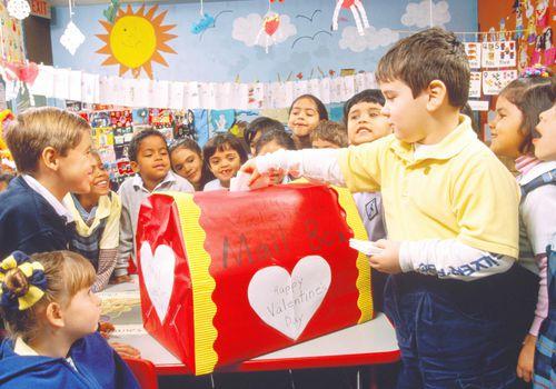 Pre-schoolers (4-5) depositing Valentine cards in box