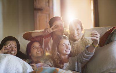 Group of smiling teenagers taking selfie on sofa in living room