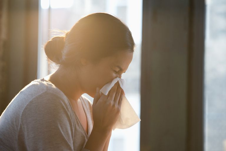 Hispanic woman wiping nose with tissue