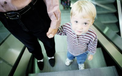 YOUNG BOY WITH MOTHER ON ESCALATOR