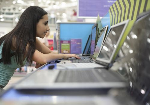 Teenage girl using a laptop in a computer store