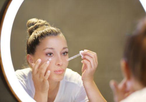 Woman applying face serum.