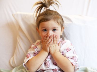 toddler in hospital bed covering her mouth