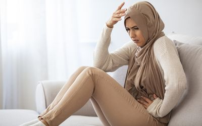 Woman experiencing acute abdominal pain as a symptom of ectopic pregnancy