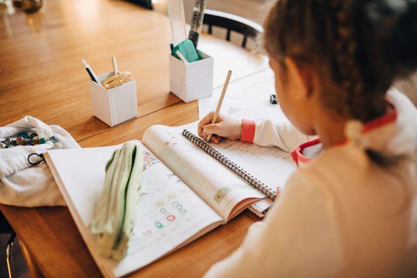 little girl writing in an activity book
