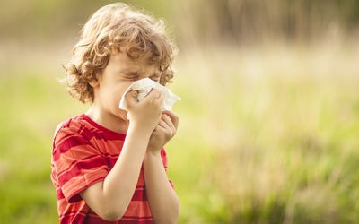 little boy blowing his nose in a field