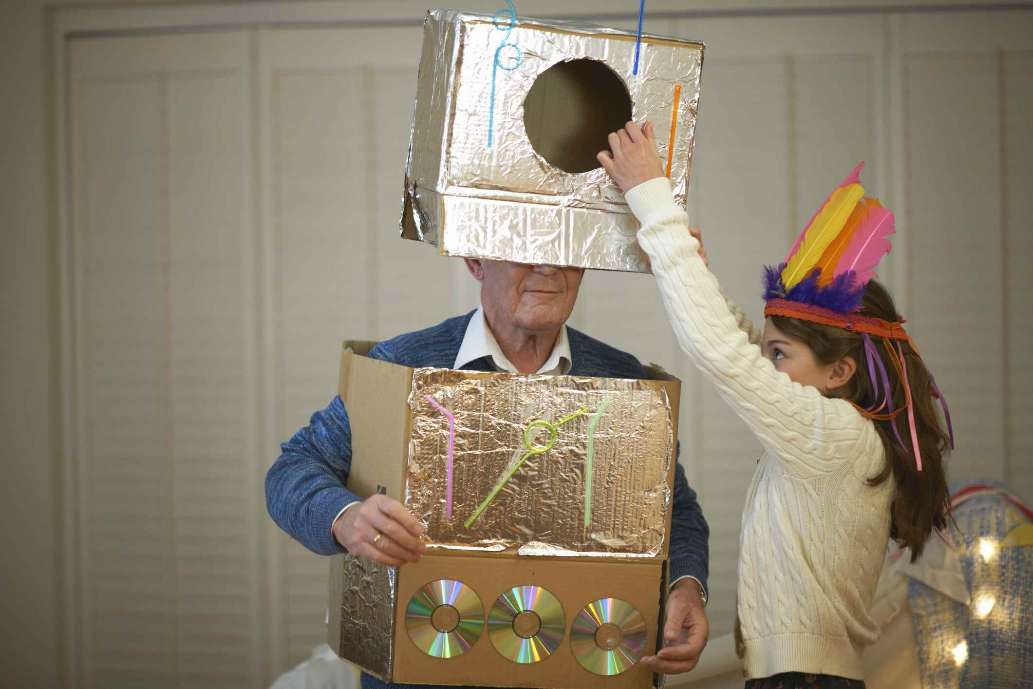 Child playing dress-up with grandparent
