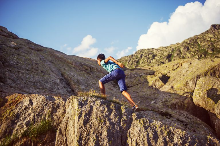 Boy climbing up rocks