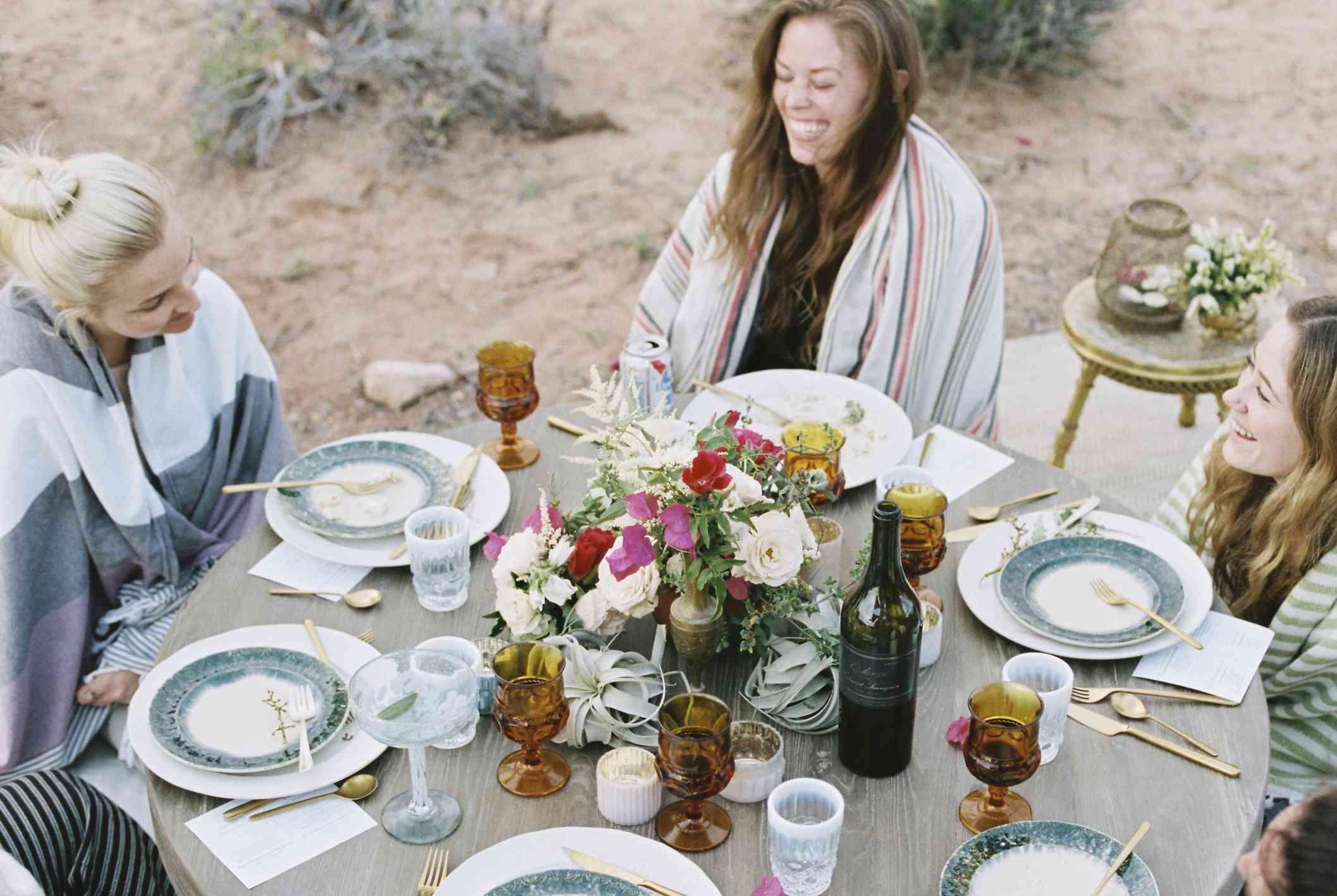 A small group of women enjoying an outdoor meal in a desert