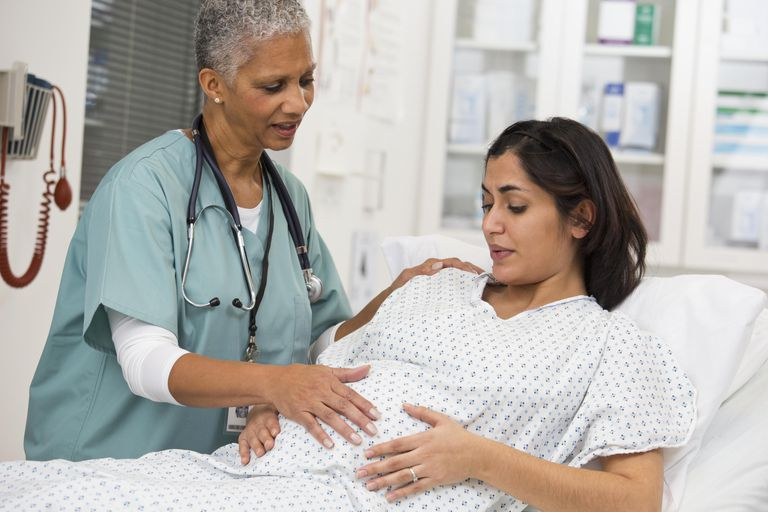 Black doctor examining pregnant patient's belly