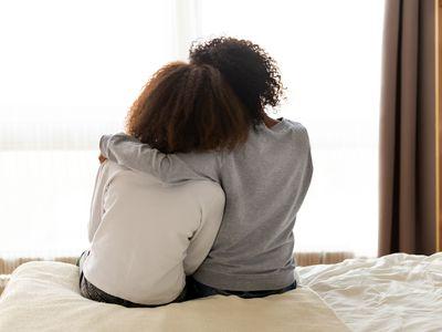 siblings hugging backs to camera