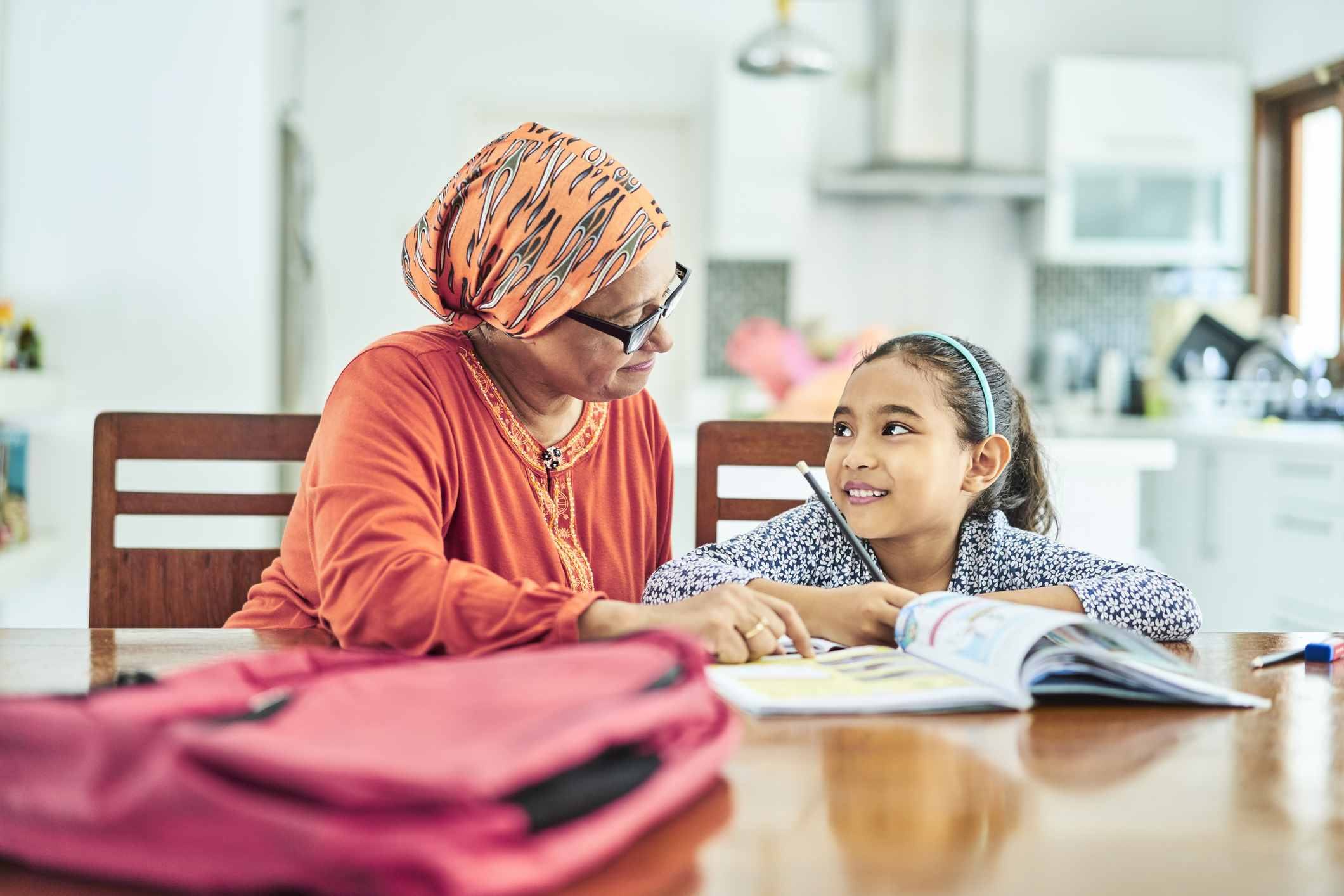 Grandmother assisting girl in studying at home