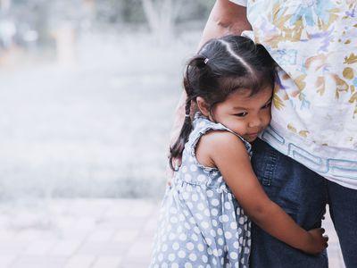 Sad little girl hugging her mother's leg