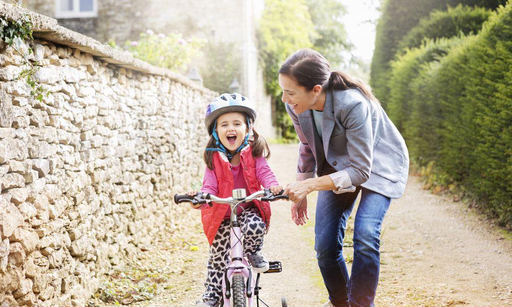 Woman pushing daughter on bicycle