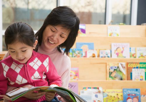 Girl (4-5) sitting on lap of teacher reading book, smiling