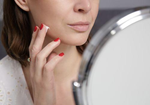 Woman putting azelaic acid cream on face