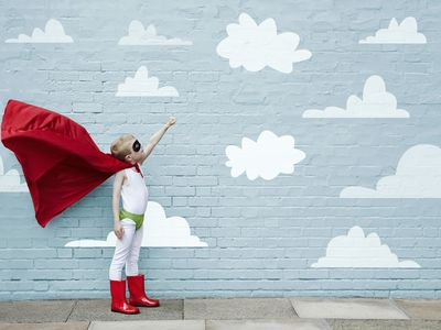 pretend play ideas - boy in superhero costume with wall and clouds