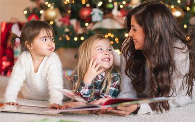 Two young sisters read in the living room by the Christmas tree with their Mom