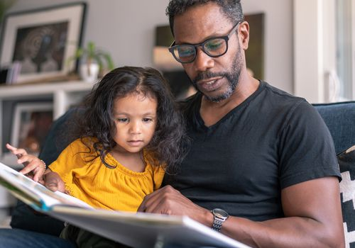 """Father reading book with daughter during """"time-in"""""""