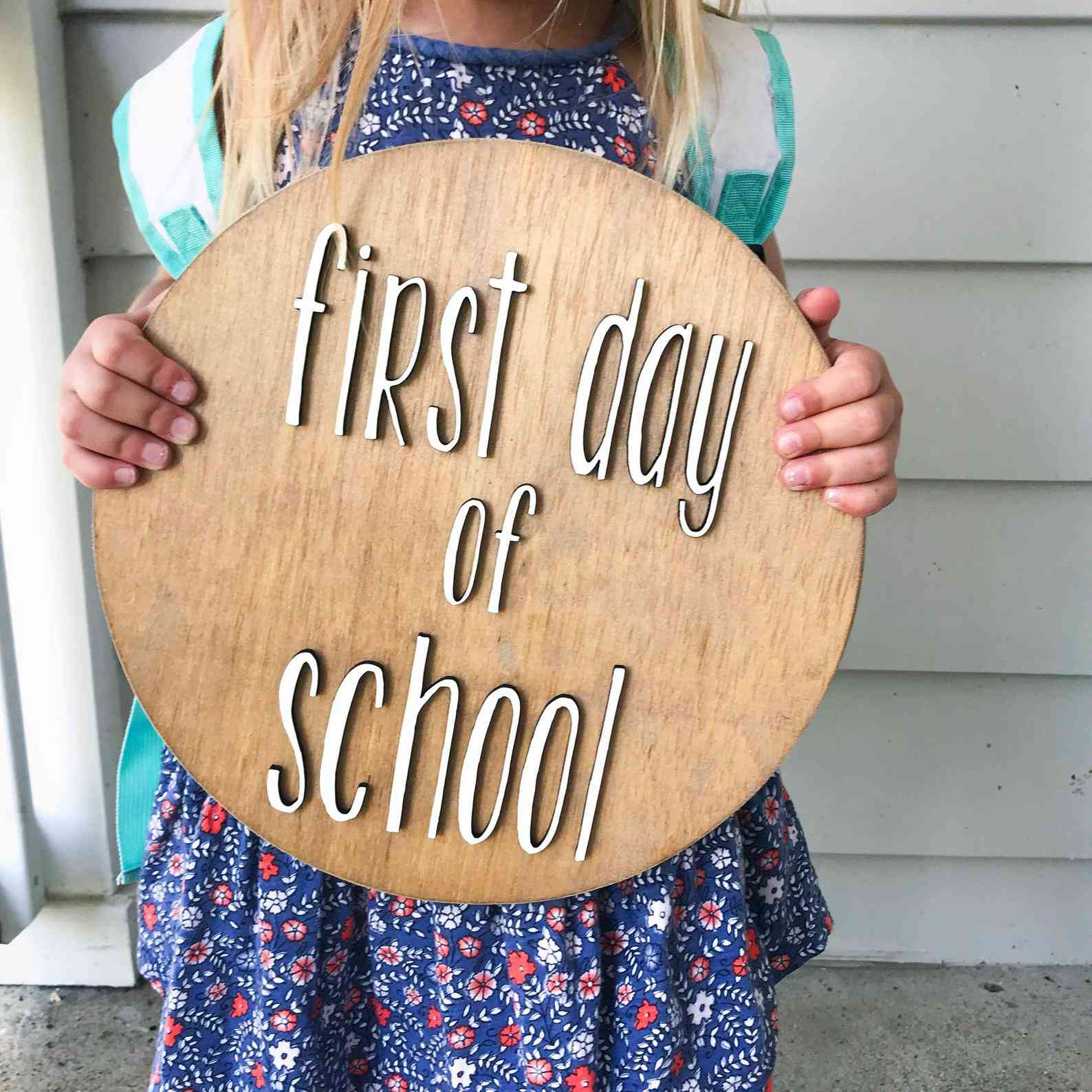 girl holding a wooden sign