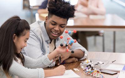 Girl draws molecule while teen helps