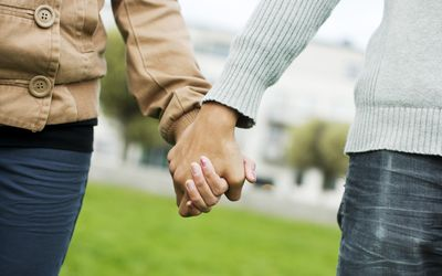Midsection of a teenage couple holding hands
