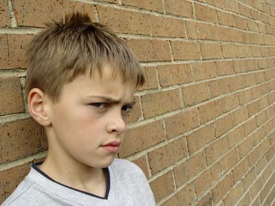 defiant little boy standing against a brick wall