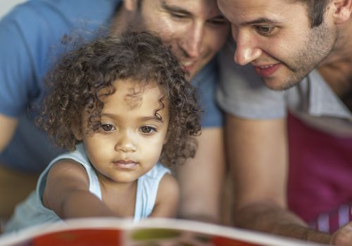 Two men with kid looking at book